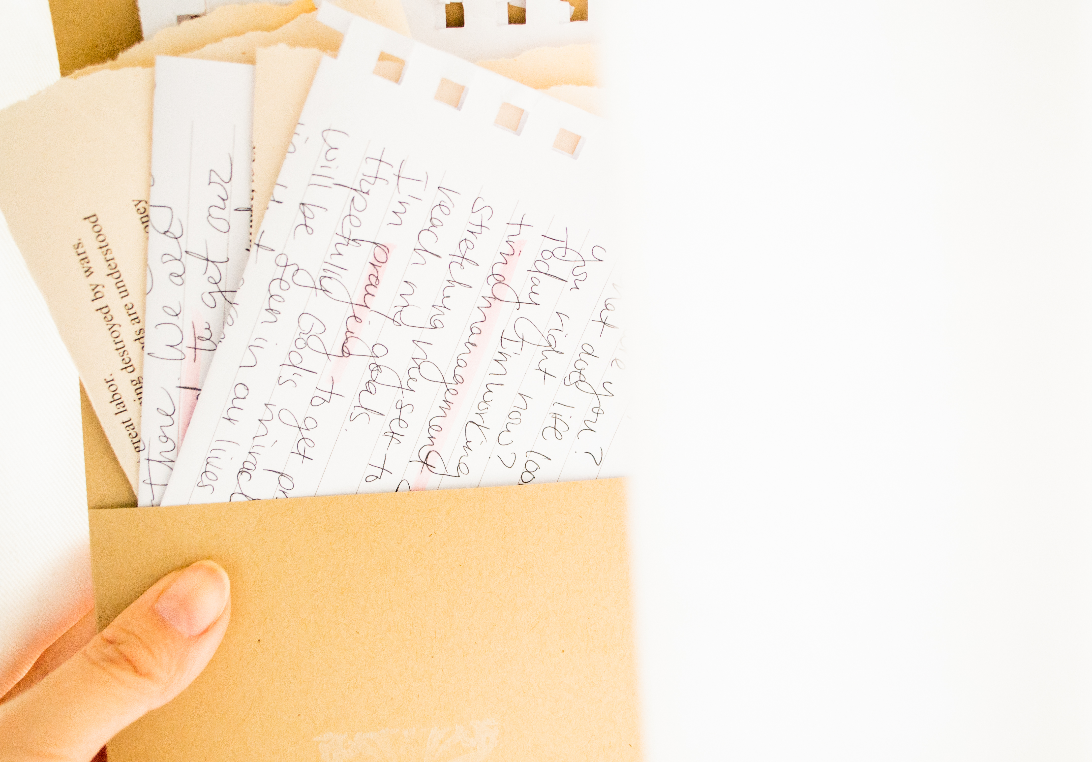 Holding an envelope with hand written note on a white fabric with lots of light
